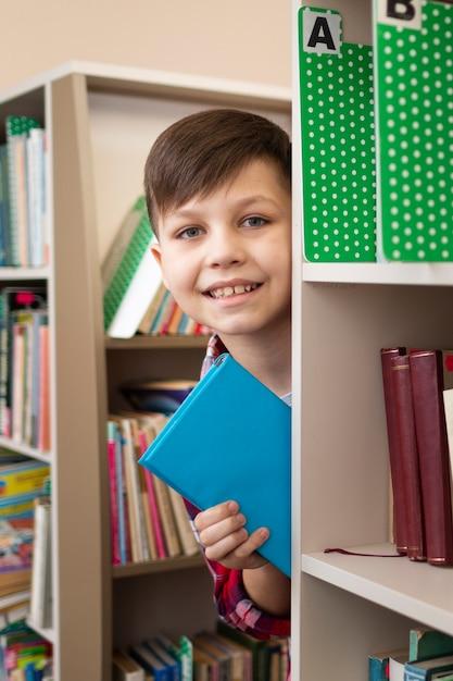 Jongen met boek tussen planken Gratis Foto