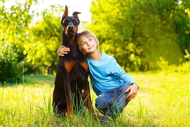 Jongen met dobermann in zomerpark. Premium Foto