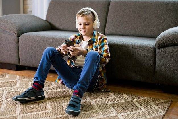 Jongen met een koptelefoon met behulp van smartphone Gratis Foto