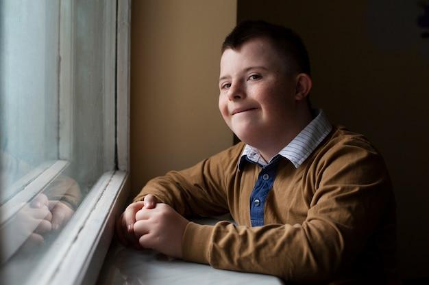 Jongen met het syndroom van down poseren door raam Premium Foto