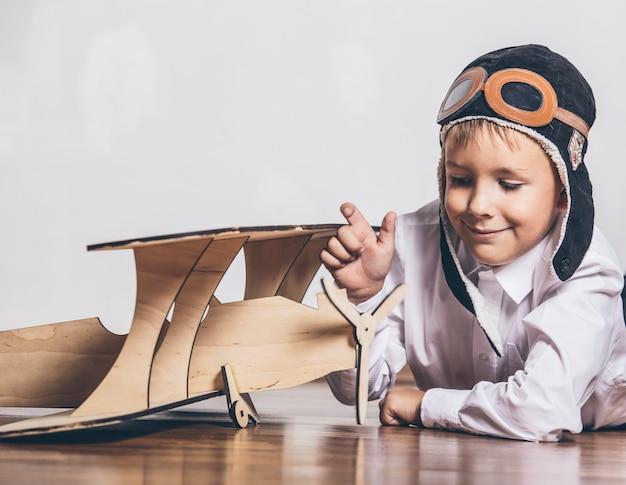 Jongen met houten vliegtuigmodel en een pet met pet Premium Foto