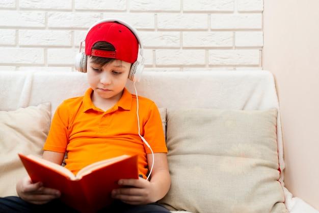 Jongen met koptelefoon lezen Gratis Foto