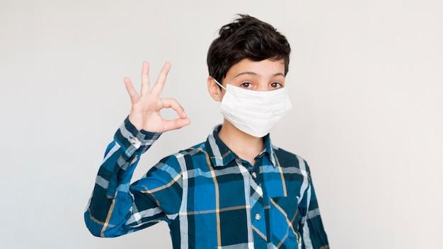 Jongen met masker dat ok teken toont Gratis Foto