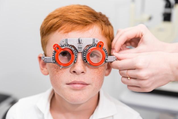 Jongen met optometrist proefkader die zijn ogen in oftalmologische kliniek testen Gratis Foto