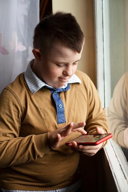 Jongen met smartphone van het syndroom van down Gratis Foto