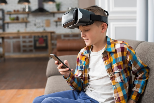 Jongen met vr headset en smartphone Gratis Foto
