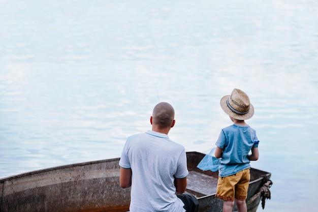 Jongen met zijn vader die op meer vissen Gratis Foto