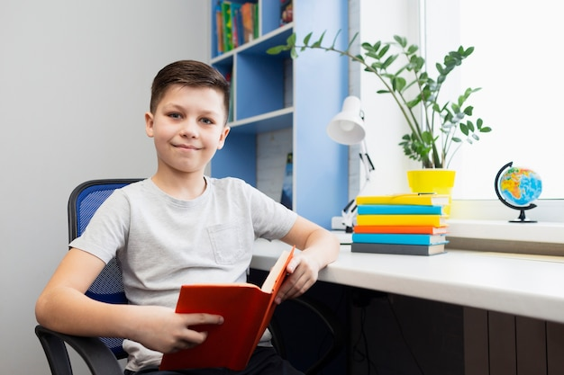Jongen op kantoor lezen Gratis Foto
