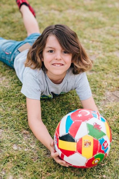 Jongen speelt met bal op gras Gratis Foto