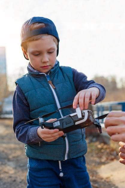 Jongen speelt met zijn drone in het park Premium Foto