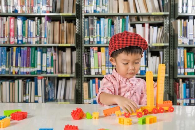 De Bibliotheek Kamer : Jongen spelen met plastic blokken in de bibliotheek kamer school