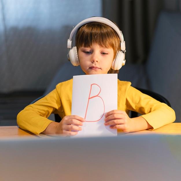 Jongen toont een papier met de letter b op virtuele cursussen Gratis Foto