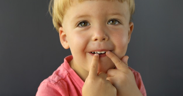 Jongen wijst zijn vingers van beide handen op zijn tanden Premium Foto