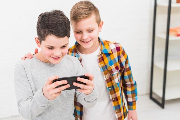 Jongens die met smartphone spelen Gratis Foto