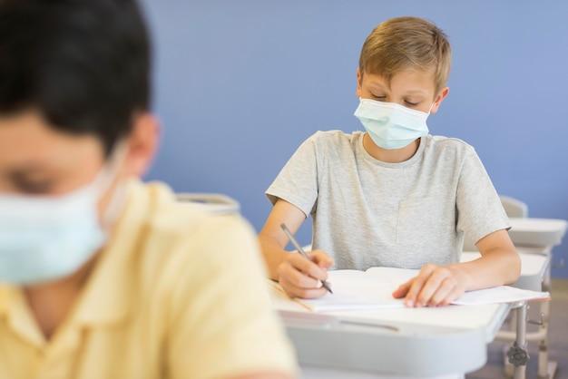 Jongens in de klas met maskers Gratis Foto