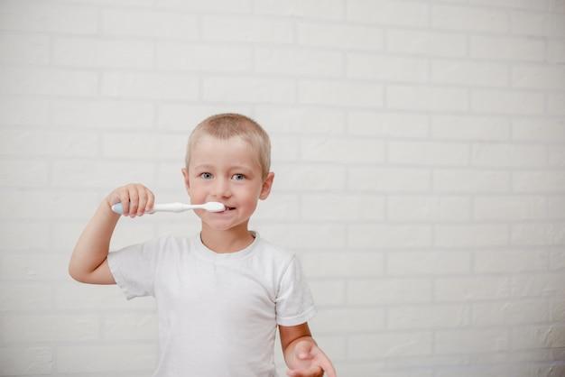 Jongens schoonmakende tanden. klein kind met een borstel witte muur Premium Foto