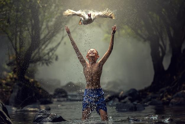 Jongens spelen met hun eend in de kreek Premium Foto