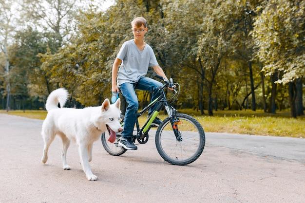 Jongenskind op fiets met witte schor hond | Premium Foto