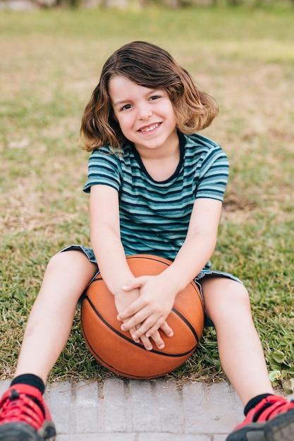 Jongenszitting in gras met basketbal Gratis Foto