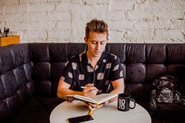 Jongenszitting op een zwarte bank en het nemen van nota's in een notitieboekje Gratis Foto