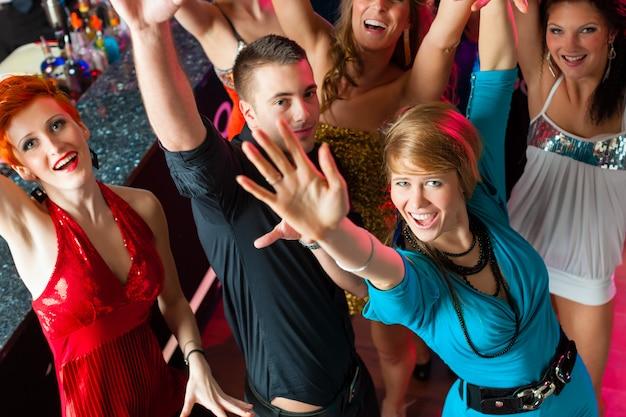 Jongeren dansen in club of disco, mannen en vrouwen Premium Foto