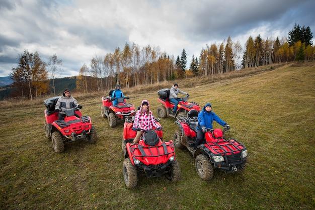 Jongeren in de winterkleren op vijf rode vierlingfietsen op een plattelandssleep in aard onder de hemel met wolken Premium Foto
