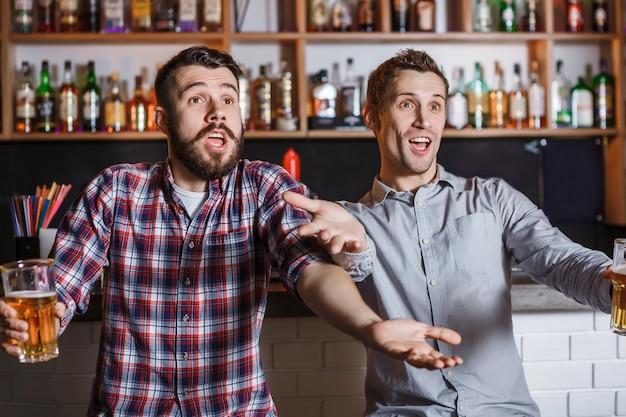 Jongeren met bier kijken voetbal in een bar Gratis Foto