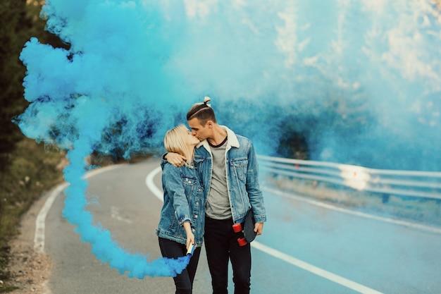Jongeren omarmen en kussen met kleurrijke blauwe rook in de hand. Premium Foto