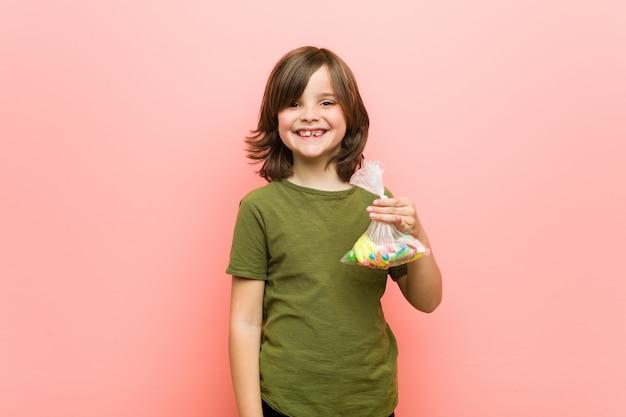 Jongetje kaukasisch bedrijf snoepjes gelukkig, glimlachen en vrolijk. Premium Foto
