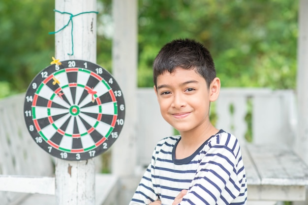 Jongetje spelen dartbord boord familie buiten activiteit Premium Foto