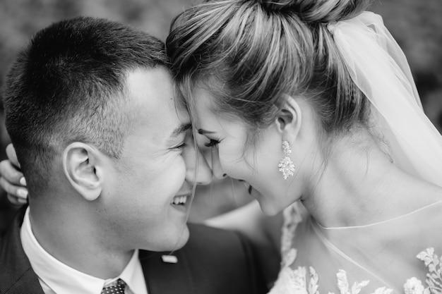 Jonggehuwden in zwart-witfotografie sloten hun ogen en leunden met hun hoofd. detailopname. Premium Foto