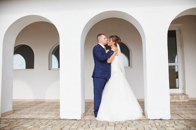 Jonggehuwden omhelzen en kussen Premium Foto