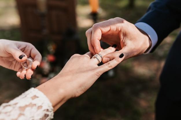 Jonggehuwden zetten ringen op, ruilen ringen, trouwringen, huwelijksceremonie, stel, jong stel, liefde, ringen. Premium Foto