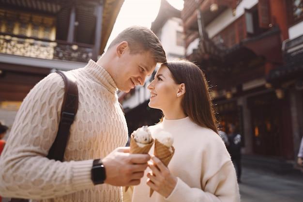 Jonggehuwdepaar die roomijs van een kegel op een straat in shanghai dichtbij yuyuan china eten. Gratis Foto