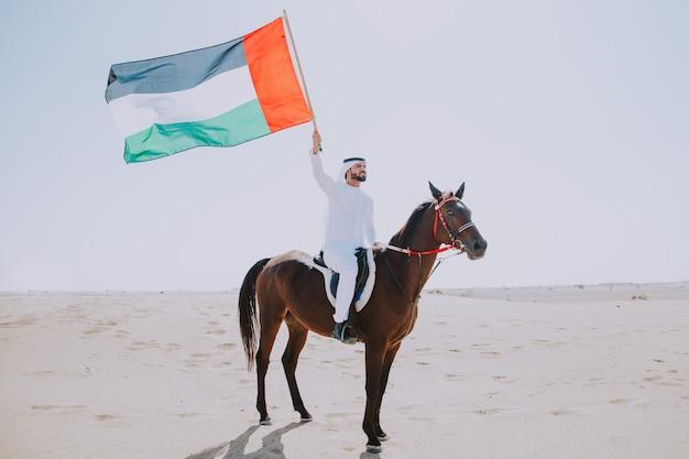 Jongvolwassene met kandura, de traditionele kleding van de emiraten, berijdend zijn paard in de woestijn Premium Foto