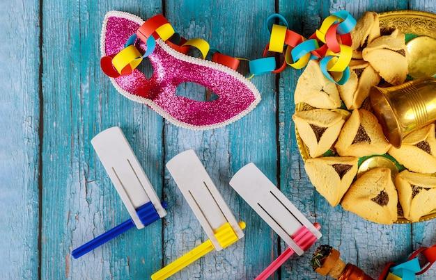 Joodse feestdag purim met hamantaschen koekjes hamans oren, carnaval masker en perkament kippa, hoorn, over rustieke achtergrond Premium Foto