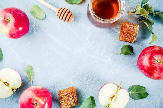 Joodse feestdag rosh hashanah of appel feest concept, met rode appels, appelbladeren en honing in pot, lichtblauw achtergrondframe Premium Foto