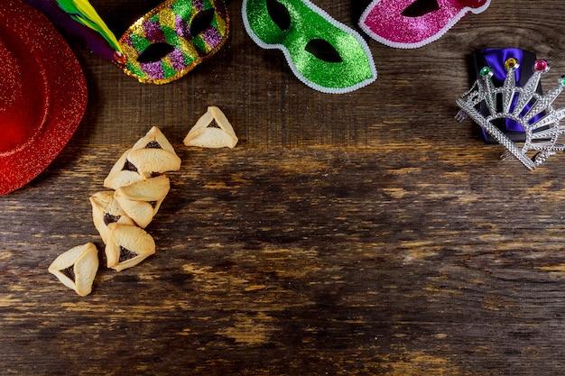 Joodse vakantie purim met carnavalmasker en hamantaschen koekjes. plat leggen Premium Foto
