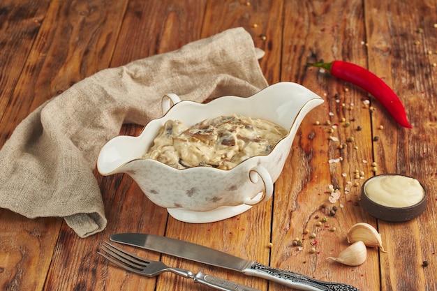 Julienne met kip, champignons en kaas in een keramische bowlon houten tafel Premium Foto