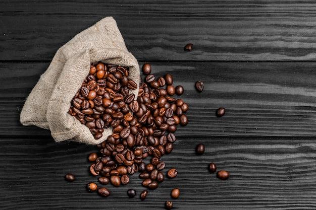 Jutezak vol gebrande koffiebonen en verspreid op een houten tafel Premium Foto