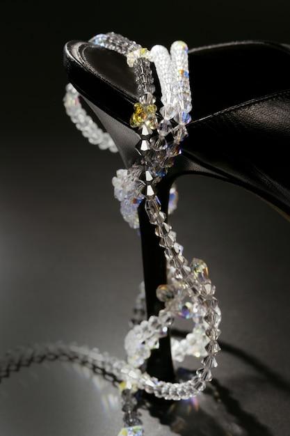 Juwelen rond een modieuze zwarte schoenhak Premium Foto