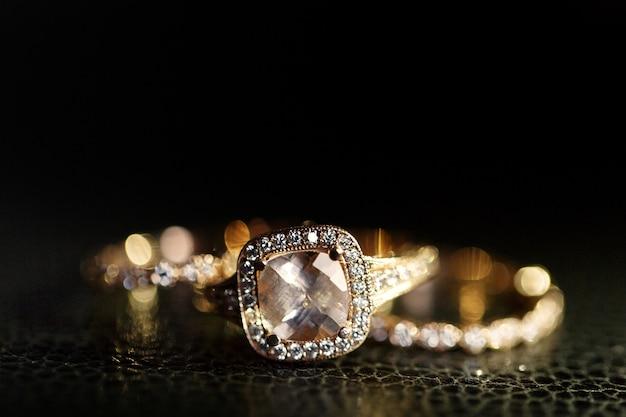 Juwelen schitteren in de gouden trouwringen die op het leer liggen Gratis Foto