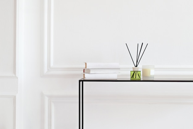 Kaars en aromatische rietverfrisser op tafel in spa salon. aroma vloeistof in glazen fles met rietstokjes. aroma diffuser in luxe in de slaapkamer. hygge. scandinavische home decor kaarsen, geur, boeken Premium Foto