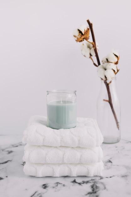 Kaars in kandelaar over gestapelde witte servetten dichtbij katoenen takje in fles Gratis Foto