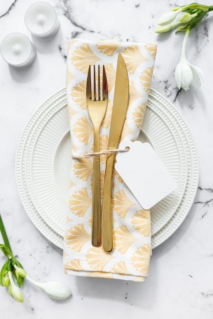 Kaarsen; bloem en witte plaat met gevouwen servet en bestek op gestructureerde achtergrond Gratis Foto