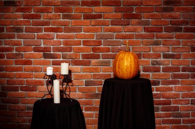 Kaarsen en pompoen op tafel over bakstenen muur. halloween. kopieer ruimte. Gratis Foto