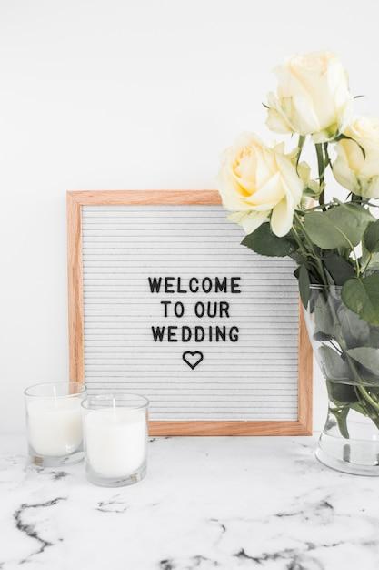 Kaarsen en vaas met welkomst bord voor bruiloft tegen witte achtergrond Gratis Foto