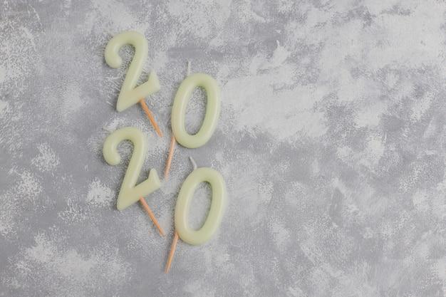 Kaarsen in de vorm van nummer 2020 als een symbool van het nieuwe jaar naast kerstvormig fonkelend snoep op een grijze tafel. bovenaanzicht, platliggend Gratis Foto