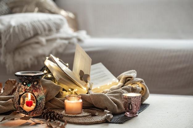 Kaarsen in kandelaars, boek, trui, slinger op de lichte ruimte van de woonkamer. Gratis Foto