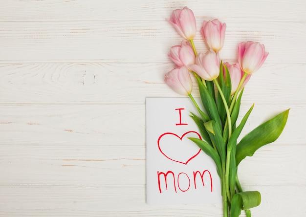 Kaart ik hou van moeder en bloemen geplaatst op witte houten tafel Gratis Foto